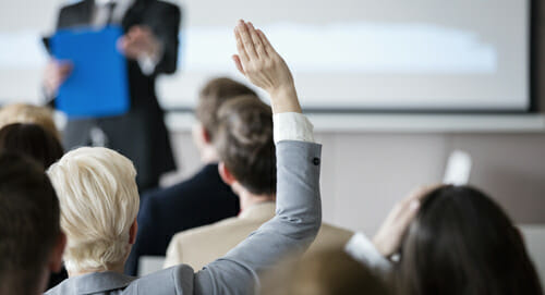 woman raising hand in training session