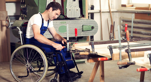 man in wheelchair working in wood shop