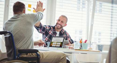 disabled man high fiving co-worker in office