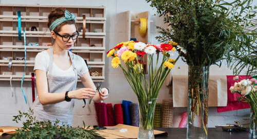 Woman on cell phone in flower shop